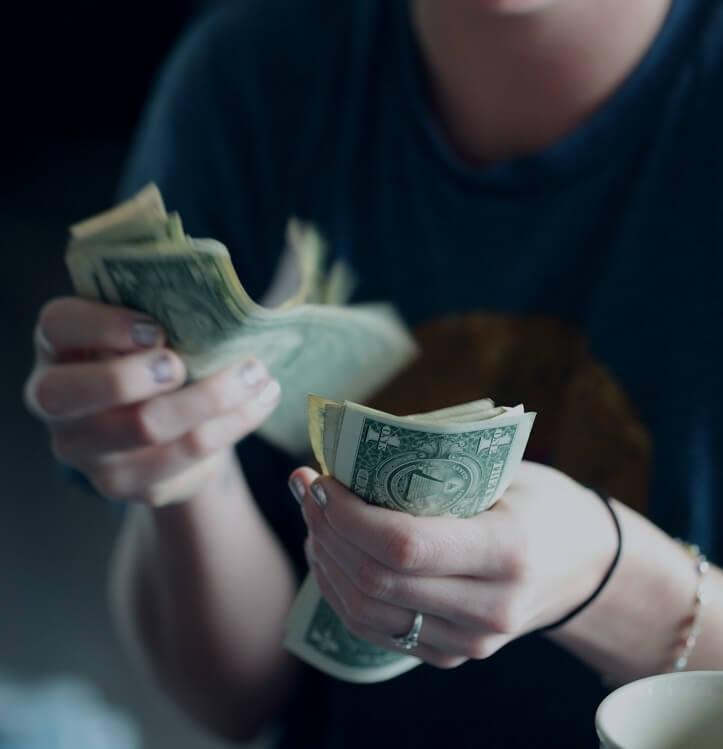 Une femme de vingt-quatre ans comptant les billets d'un dollar.