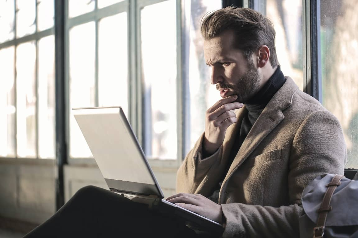 Homme se tenant le menton devant son ordinateur, en plein questionnement