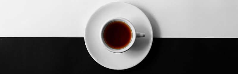 Tasse de café noir sur fond noir et blanc